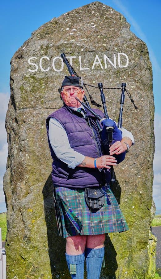 Il suonatore di cornamusa scozzese accoglie favorevolmente gli ospiti in Scozia al confine fotografia stock libera da diritti
