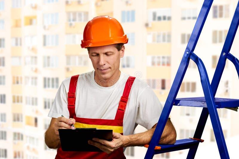 Il supervisore della costruzione scrive sulla lavagna per appunti immagini stock libere da diritti