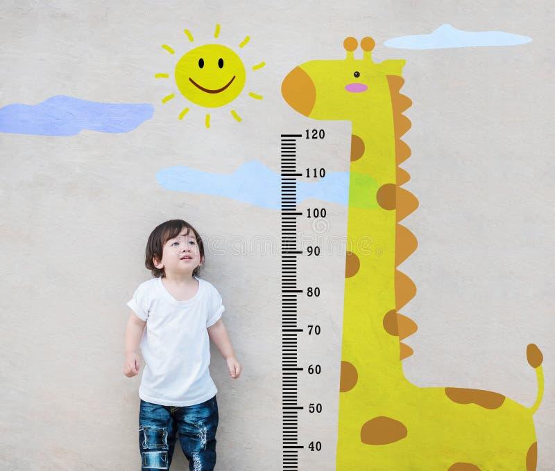 Il supporto asiatico del bambino del primo piano per altezza della misura e lo sguardo al fumetto sveglio della giraffa alla pare immagine stock
