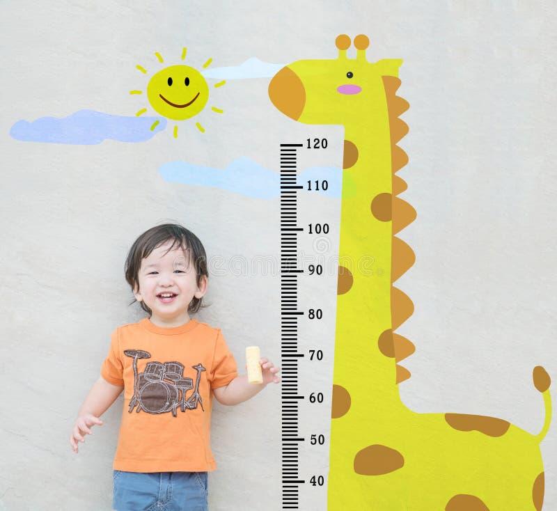 Il supporto asiatico felice del bambino del primo piano per altezza della misura con il fumetto sveglio alla parete di pietra di  fotografie stock
