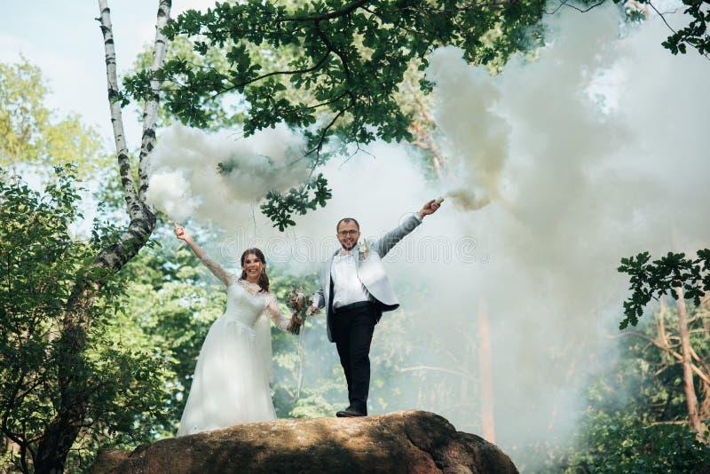 Il supporto dello sposo e della sposa su una scogliera e tenere le bombe fumogene in loro mani nel bianco immagini stock