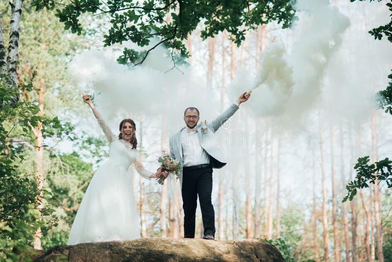 Il supporto dello sposo e della sposa su una scogliera e tenere le bombe fumogene in loro mani nel bianco fotografia stock libera da diritti