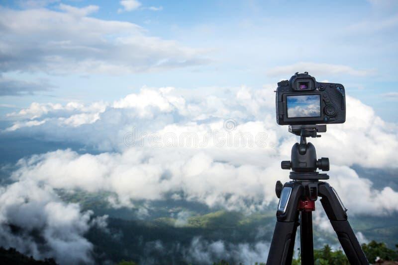 Il supporto professionale digitale della macchina fotografica di Dslr sul treppiede che fotografa la montagna, il cielo blu e la  fotografia stock