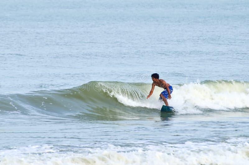 Il surfista guida il lato posteriore di un'onda durante il monsone alla spiaggia di Teluk Cempedak, Pahang, fotografia stock libera da diritti
