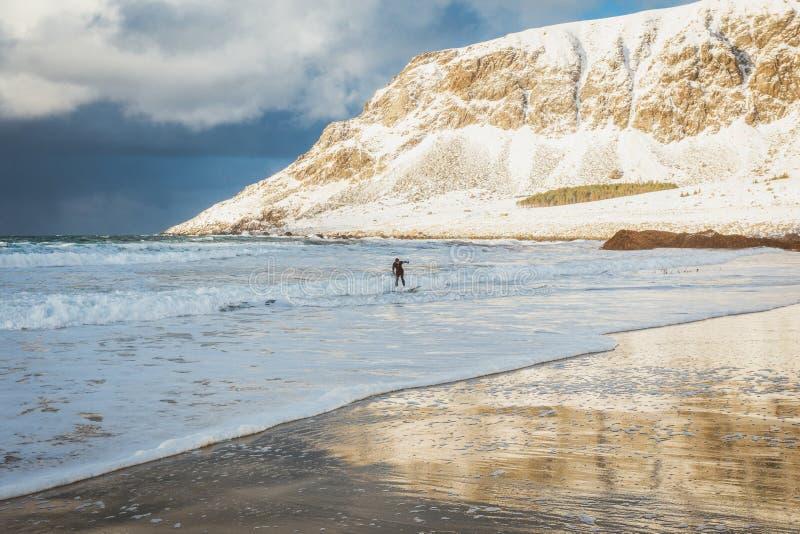 Il surfista guida le onde nell'orario invernale su una spiaggia molto bella circondata dalle montagne in Norvegia nell'inverno immagini stock libere da diritti