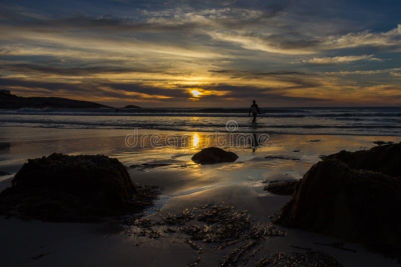 Il surfista solo cammina nel mare sotto un cielo drammatico del tramonto immagini stock