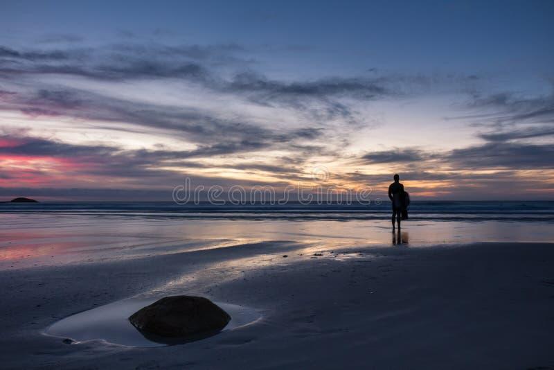 Il surfista solo sta sulla spiaggia che guarda fuori al mare immagine stock