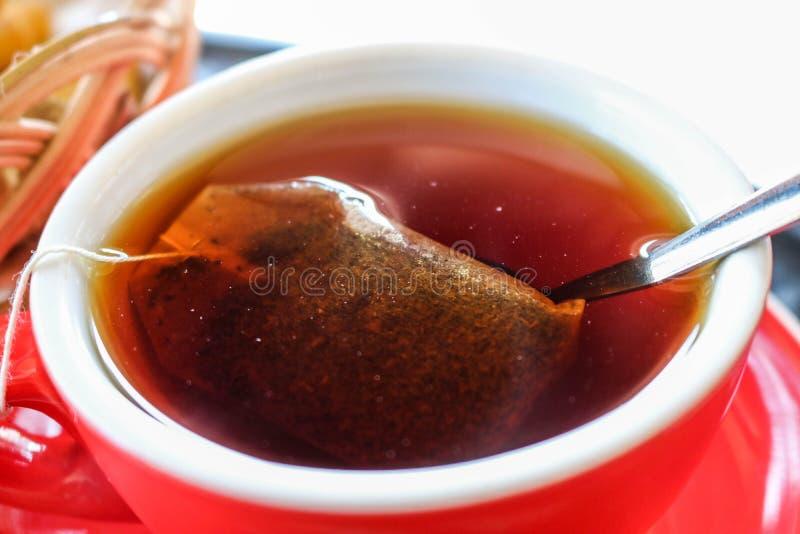 Il tè caldo in una tazza rossa immagini stock