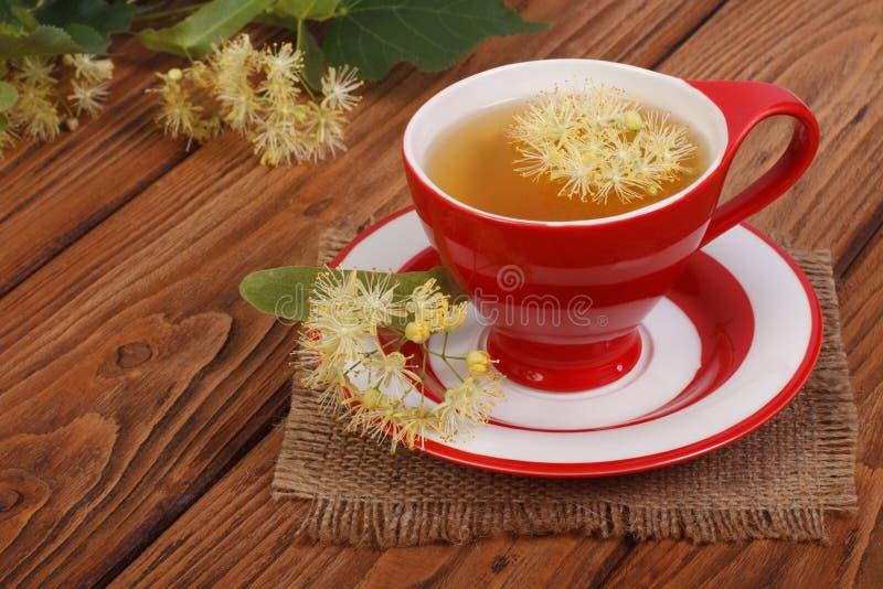 il tè con il tiglio fiorisce su una tavola di legno marrone fotografie stock