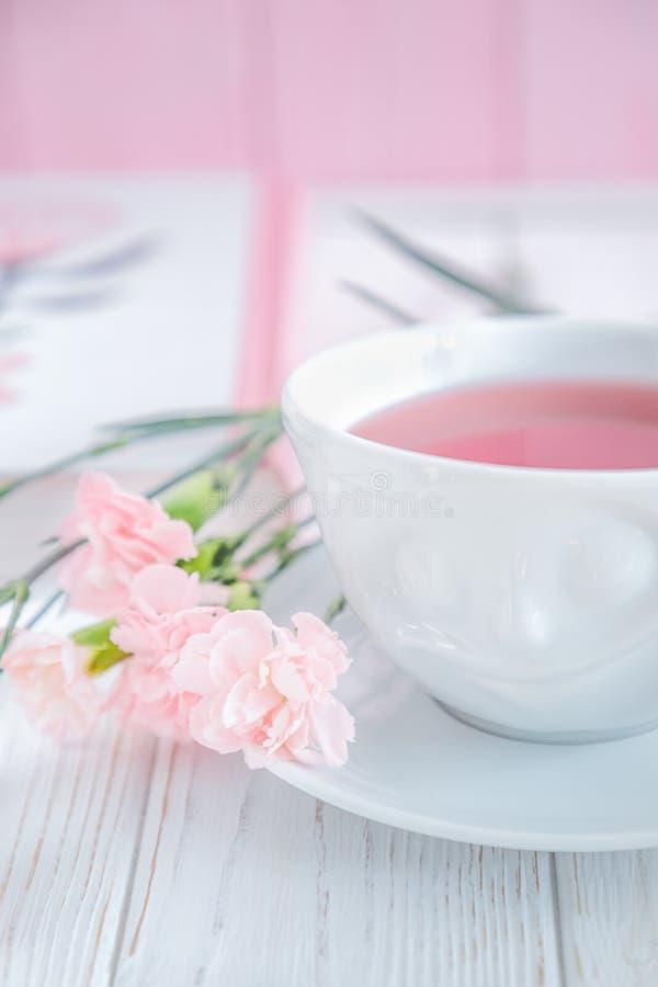 Il tè della frutta in tazza bianca ed in garofano rosa fiorisce su un fondo bianco Spazio libero immagini stock libere da diritti