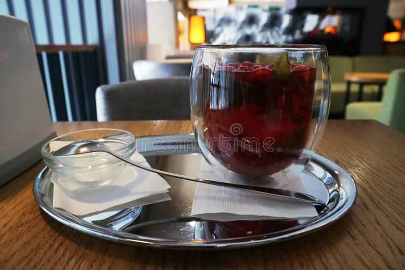 Il tè della frutta in una tazza di vetro è sulla tavola contro l'interno del caffè fotografia stock