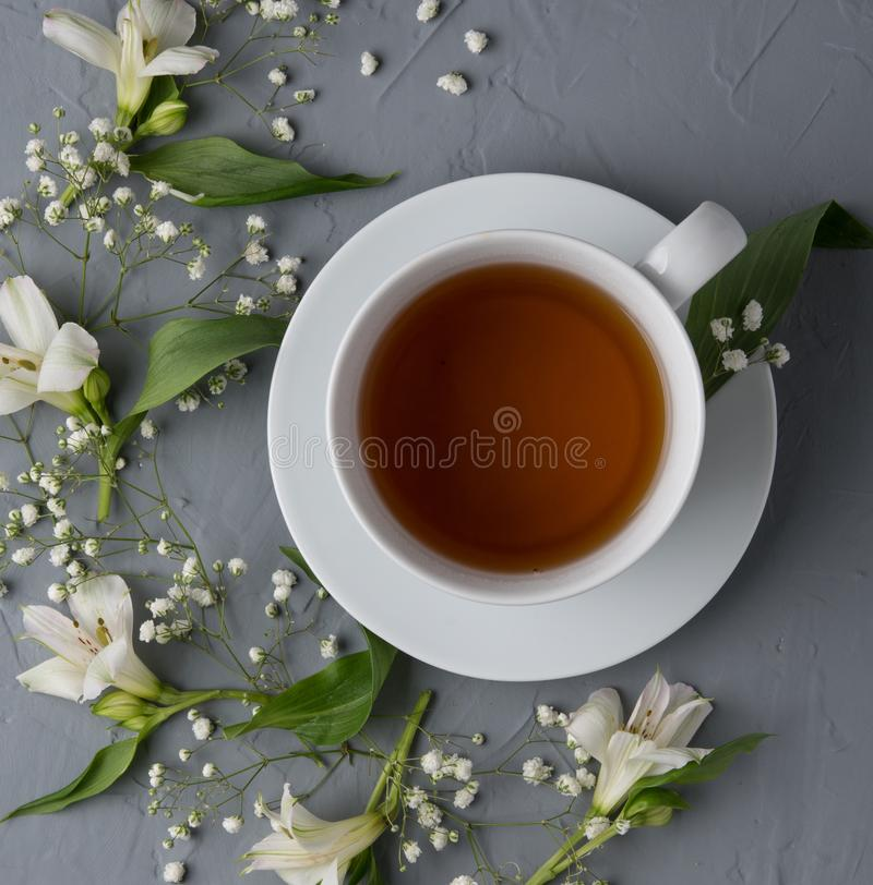 Il tè nero, fiori bianchi, sorgente di acqua calda della tazza di vista superiore fiorisce il legno romantico immagini stock