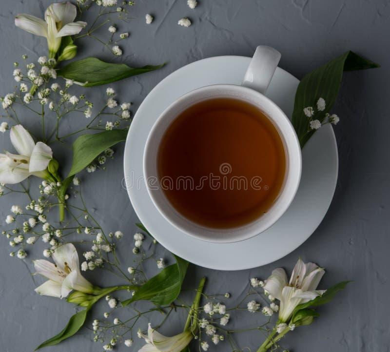 Il tè nero, fiori bianchi, sorgente di acqua calda della tazza di vista superiore fiorisce il legno romantico fotografia stock