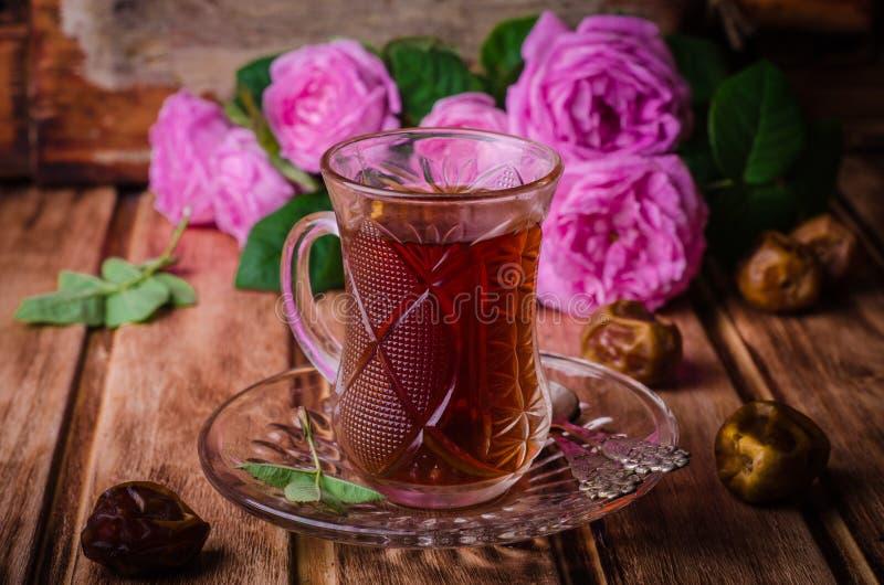 Il tè turco in una tazza di vetro e nei datteri secchi fruttifica su fondo di legno Alimento del Ramadan Fuoco selettivo immagini stock