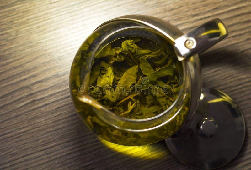 Il tè verde caldo ha fatto in una teiera di vetro sul fondo grigio del ristorante della tavola fotografia stock libera da diritti