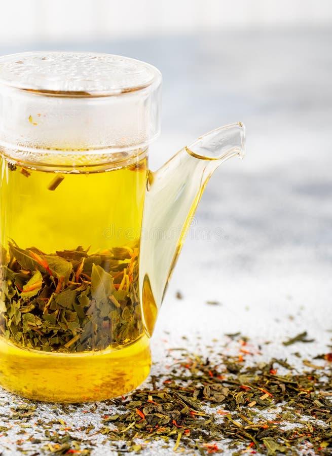 Il tè verde con la fragola fiorisce in teiera sulla tavola grigia su lig fotografia stock libera da diritti