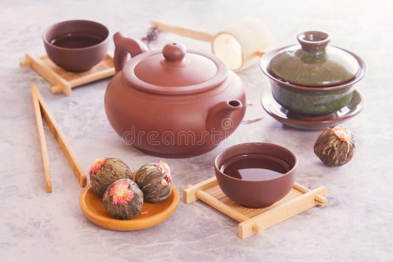 Il tè verde in germogli, teiera ceramica marrone con una tazza ha preparato per una cerimonia di tè asiatica tradizionale fotografia stock