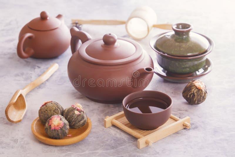 Il tè verde in germogli, teiera ceramica marrone con una tazza ha preparato per un supporto asiatico tradizionale di cerimonia di fotografia stock