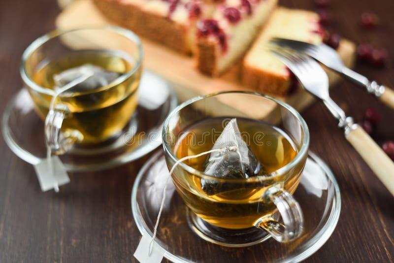 Il tè verde ha fatto in bustine di tè della piramide in tazze e torta di vetro della bacca immagini stock
