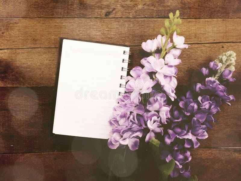 Il taccuino aperto con una pagina in bianco e decora il colore d'annata del filtro dai fiori fotografie stock