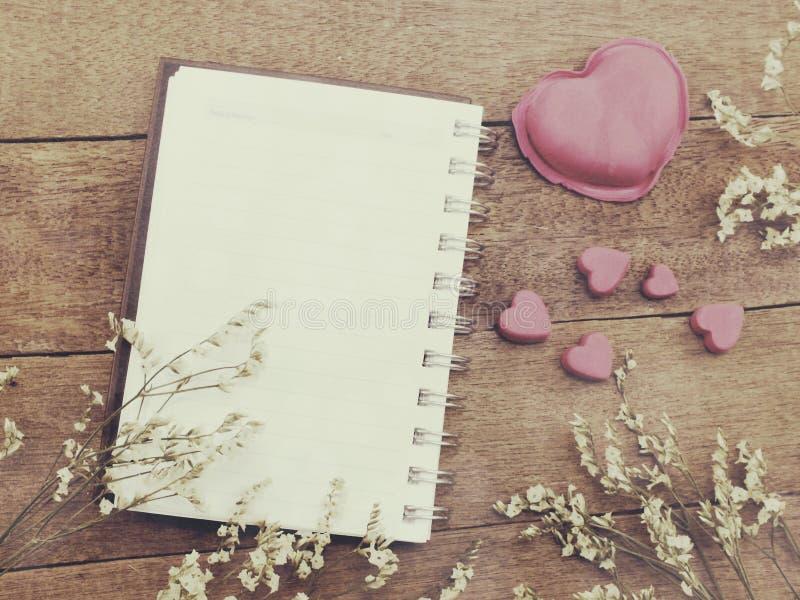 Il taccuino aperto con una pagina in bianco e decora il colore dei filtri dall'annata fotografia stock