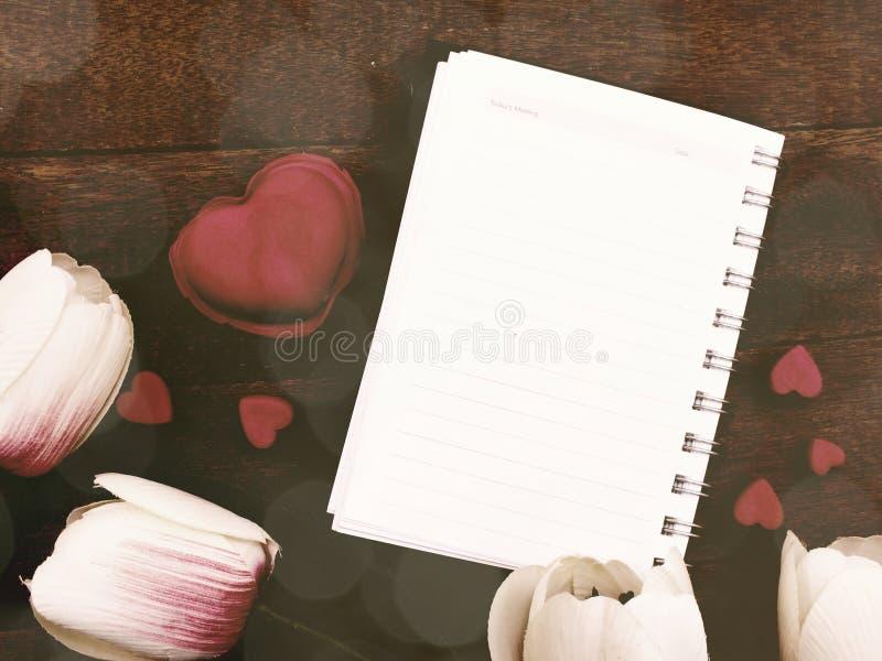 Il taccuino aperto con una pagina in bianco ed i fiori del tulipano decora fotografia stock libera da diritti