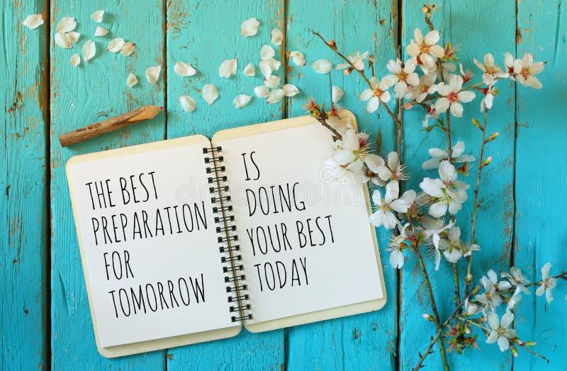 Il taccuino aperto sopra la tavola di legno con il detto motivazionale la migliore preparazione per il domani sta facendo oggi il fotografie stock