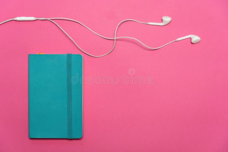 Il taccuino blu variopinto con il trasduttore auricolare bianco per ascolta la musica quando disposizione di studio o del lavoro  immagini stock