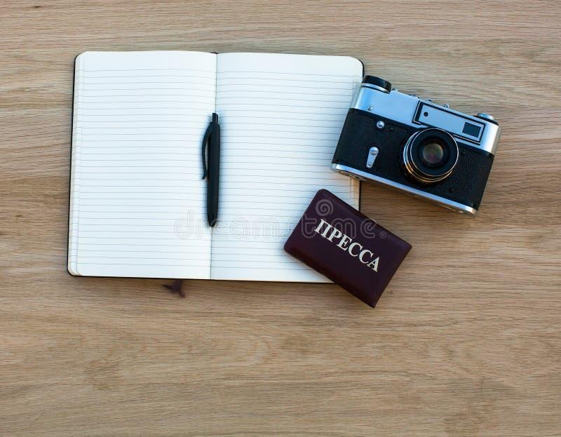 Il taccuino con la penna, la macchina fotografica ed il Russo premono l'identificazione Affare immagine stock