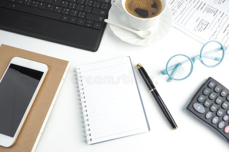 Il taccuino della pagina in bianco sul desktop bianco con la penna, caffè, lapto immagini stock libere da diritti