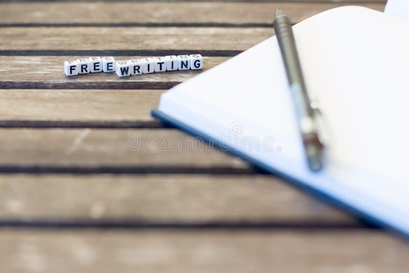 Il taccuino e il pensil sulla tavola con le lettere di bianco liberano la scrittura sul fondo di legno di marrone scuro Concetto  fotografia stock