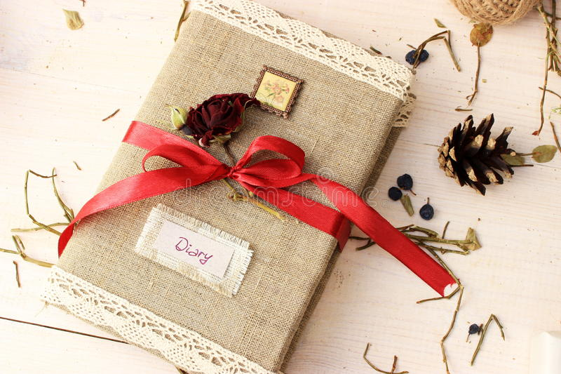 Il taccuino per la scrittura dei sogni e le memorie decorati con il nastro rosso luminoso e svegli asciugano rosa Concetto romant immagini stock