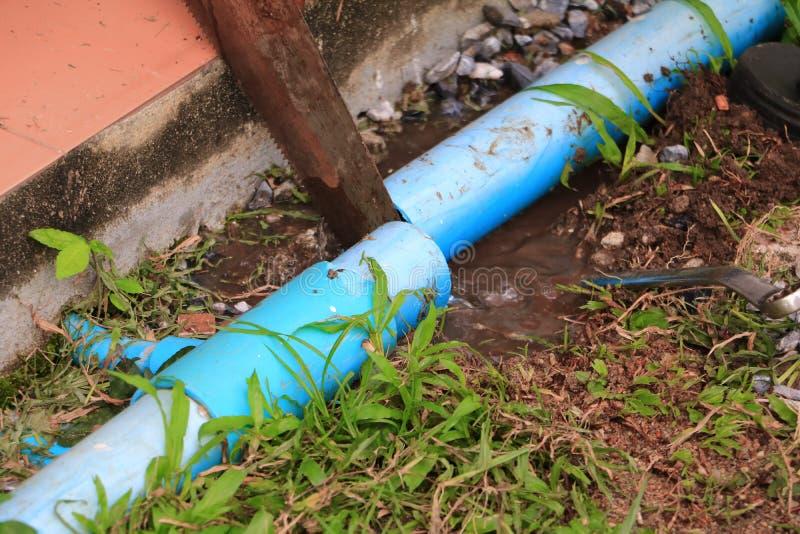 Il taglio dell'idraulico con ha visto la riparazione, scandagliante il tubo rotto fotografia stock