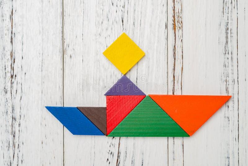 Il tangram di legno ha modellato come una gente che si siede sulla barca immagine stock