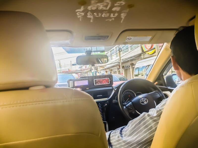 Il tassista ed il passeggero nel lato l'automobile del taxi durante vanno alla destinazione con ingorgo stradale a Bangkok, Taila fotografia stock libera da diritti