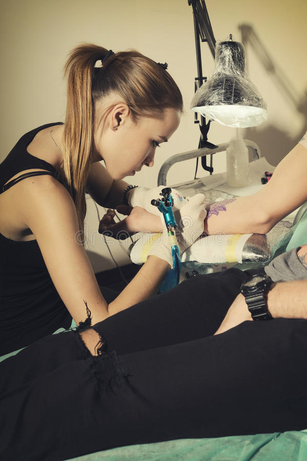Il tatuatore matrice della donna fa il tatuaggio a disposizione su una somiglianza blu di un tatuaggio futuro immagine stock libera da diritti