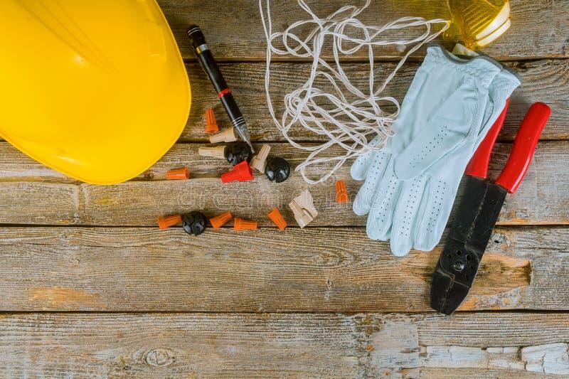 Il tecnico dell'elettricista sul lavoro prepara gli strumenti ed i cavi utilizzati nell'installazione elettrica ed in casco giall fotografie stock