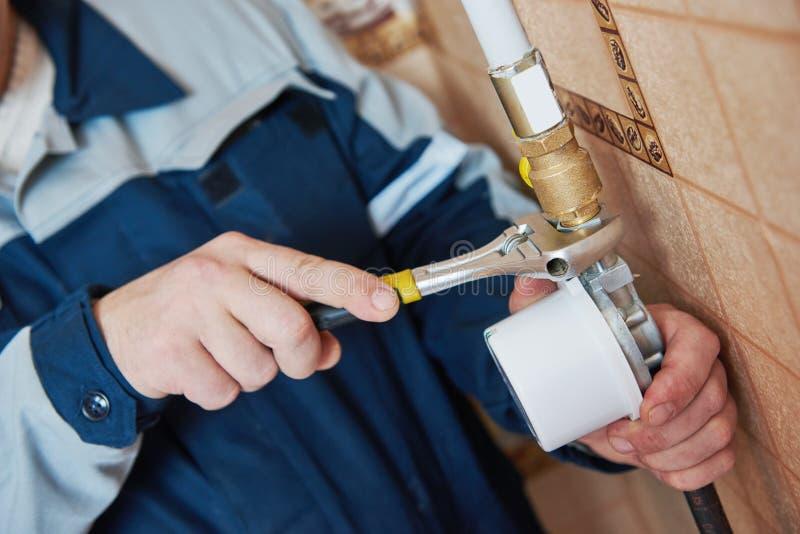 Il tecnico dell'idraulico lavora con il contatore del gas immagini stock libere da diritti