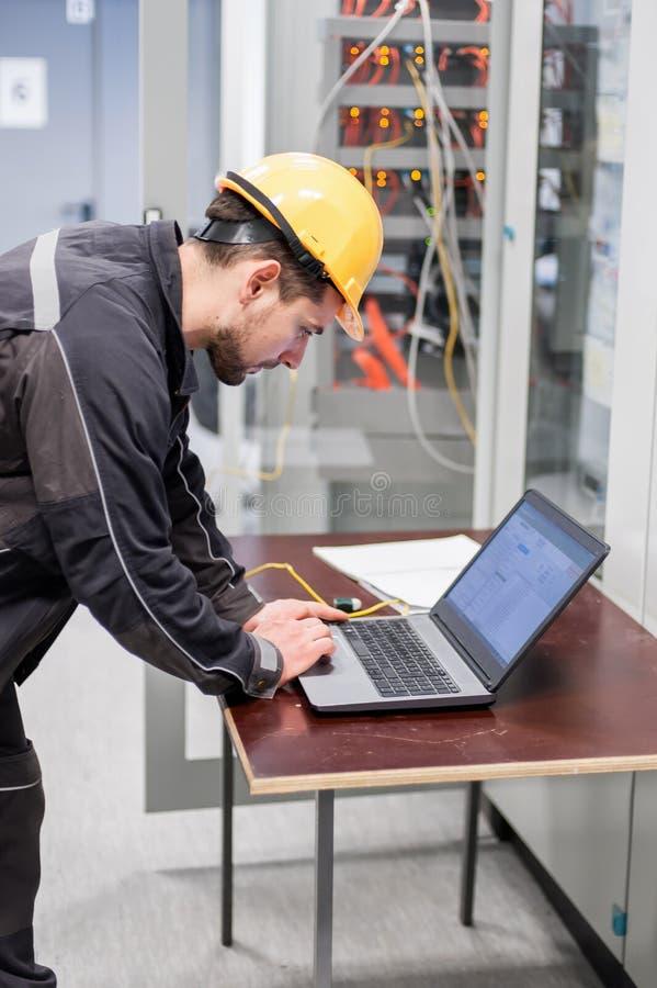 Il tecnico di assistenza ispeziona il sistema di protezione del relè con lapt immagine stock libera da diritti