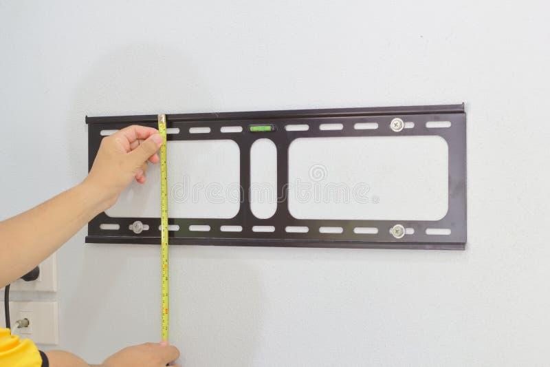 Il tecnico installa il dispositivo per appendere la TV sulla parete fotografia stock libera da diritti