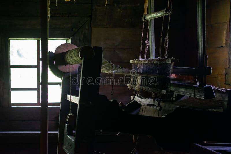 Il telaio per tessitura antico in un interno di una capanna di legno del ceppo immagini stock libere da diritti