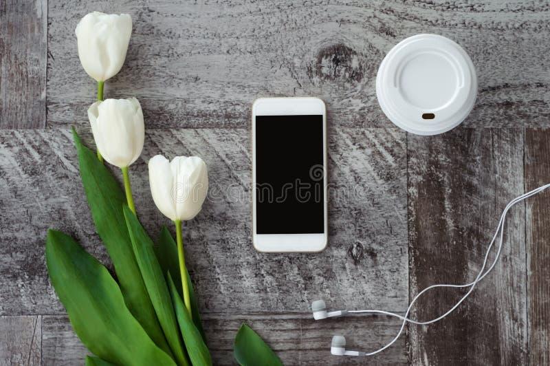Il telefono bianco con le cuffie, il caff? ed i fiori sono sulla tavola Lavoro a casa freelance immagini stock libere da diritti