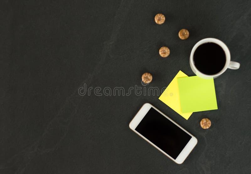 Il telefono bianco con una tazza di caff?, di autoadesivi colorati multi per le note ed i dolci sono su una tavola nera fotografie stock libere da diritti
