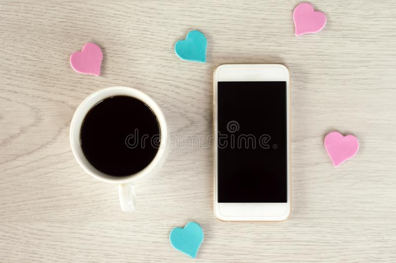 Il telefono bianco con una tazza di caff? ed i piccoli cuori si trovano su una tavola di legno bianca fotografia stock