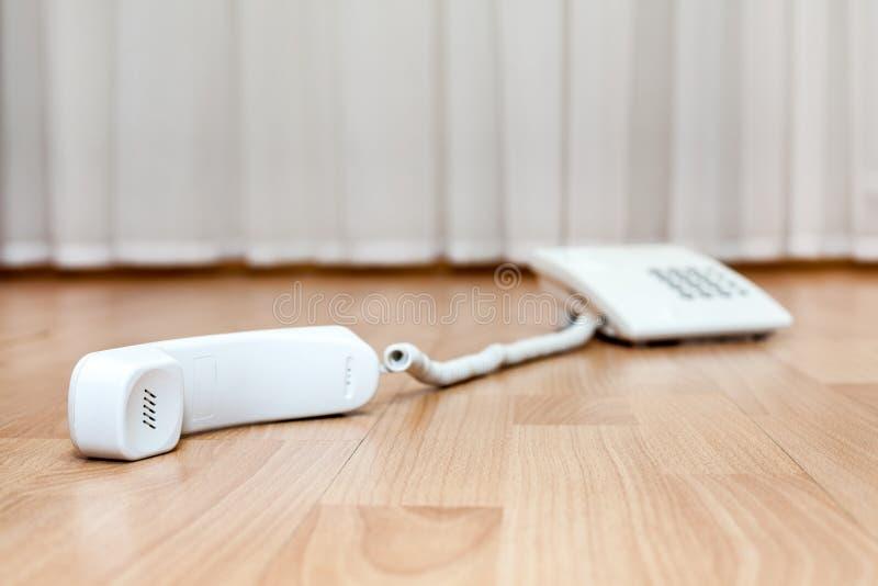 Il telefono bianco della linea terrestre è sul pavimento con il microtelefono caduto immagine stock