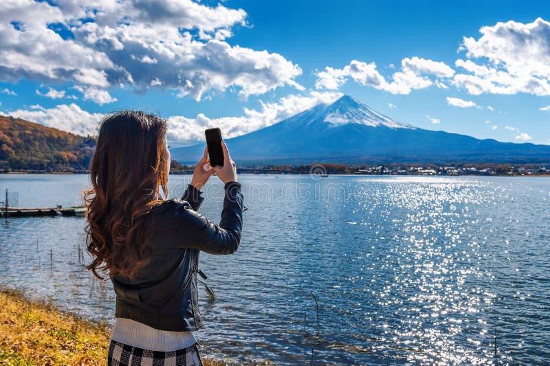 Il telefono cellulare di uso della donna prende una foto alle montagne di Fuji, lago Kawaguchiko nel Giappone immagini stock