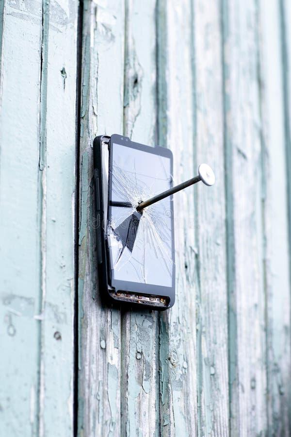 Il telefono cellulare difettoso è inchiodato ad un vecchio recinto fotografia stock