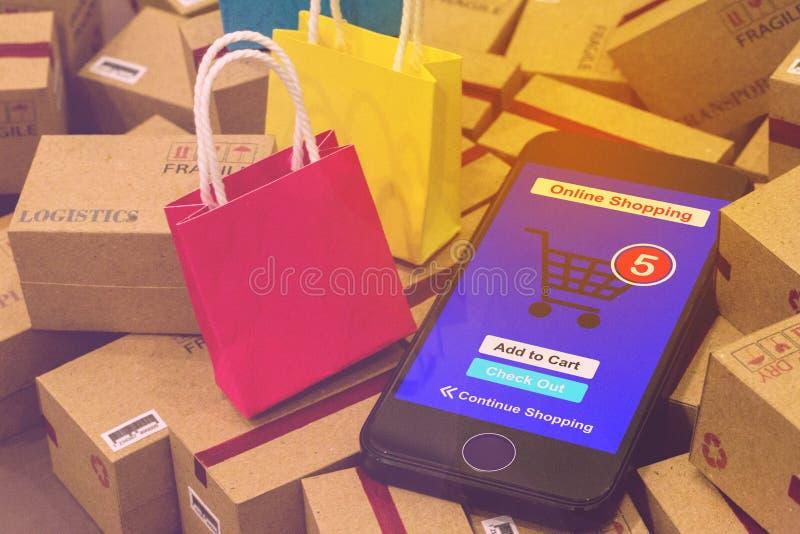Il telefono cellulare esegue un app di compera online messo vicino a piccolo pape rosso immagine stock libera da diritti