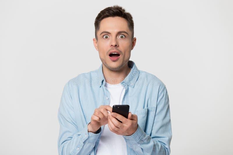 Il telefono colpito della tenuta dell'uomo stupito dalle notizie online posa all'interno immagini stock