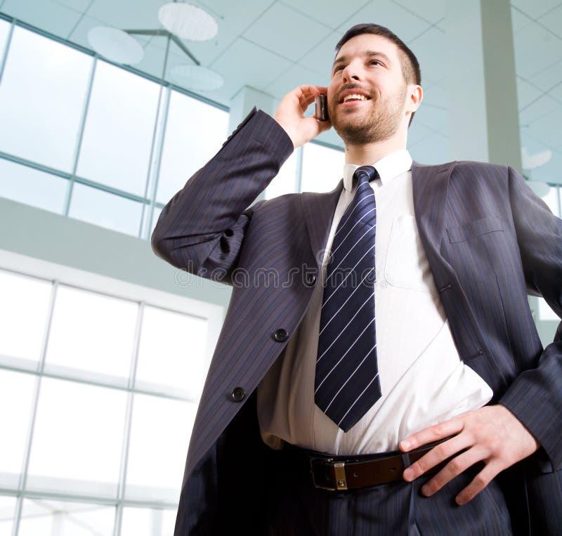 il telefono dell'uomo d'affari parla fotografia stock